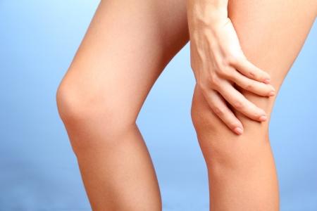 de rodillas: mujer con dolor en la rodilla, sobre fondo azul