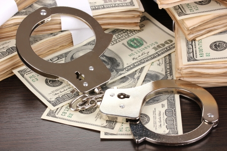 Handcuffs and packs of dollars on wooden table close-up Stock Photo - 14936726