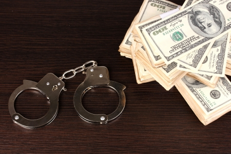 Handcuffs and packs of dollars on wooden table close-up Stock Photo - 14956029