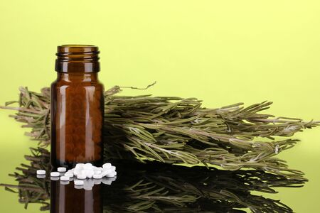 bottle with pills and herbs on green background. concept of homeopathy photo