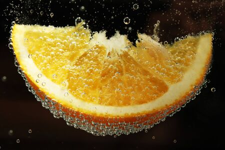 slice of orange in the water with bubbles, on black background photo