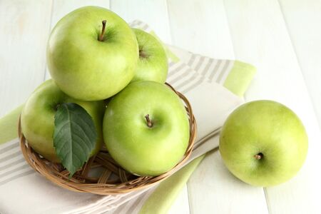 Ripe green apples with leaves in basket, on wooden table Stock Photo - 14954843