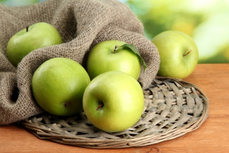 green apple: Ripe green apples with leaves on burlap, on wooden table, on green background Stock Photo
