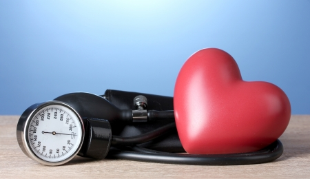 blood supply: Black tonometer and heart on wooden table on blue background