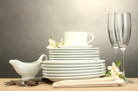 empty clean plates, glasses and cup on wooden table on grey background photo