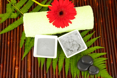 cosmetic clay for spa treatments on bamboo background close-up photo