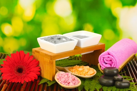 cosmetic clay for spa treatments isolated on colorful green background photo