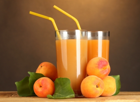 glasses of apricot juice on wooden table on brown background Stock Photo - 15009133