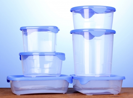 wooden lid: Plastic containers for food on wooden table on blue background Stock Photo