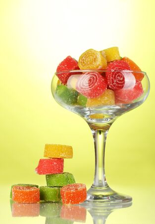 colorful jelly candies in  in cocktail glass on green background  photo