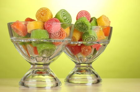 colorful jelly candies in  in glass bowls on green background  photo
