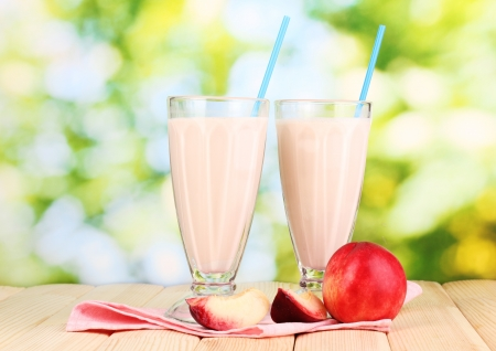 Peach milk shakes on wooden table on bright background photo