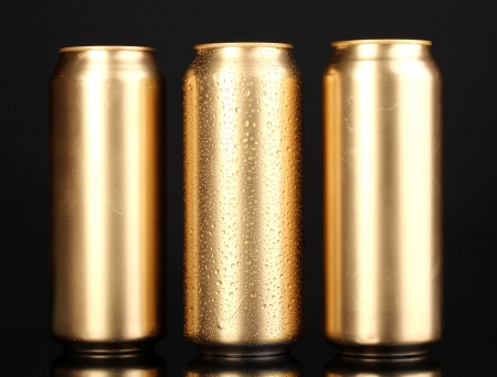 golden cans with water drops isolated on black photo