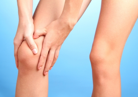knee joint: woman holding sore knee, on blue background