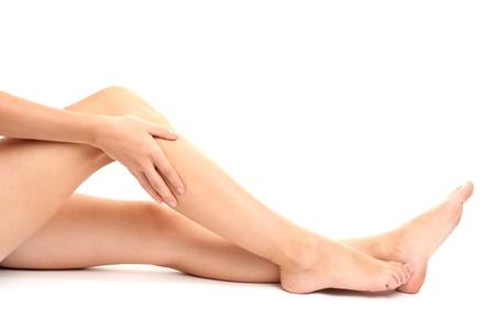 woman holding sore leg, isolated on white