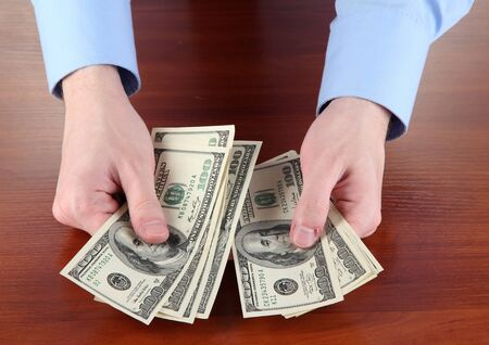 recounts: man recounts dollars on a wooden table close-up Stock Photo