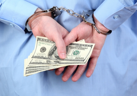 man in handcuffs is holding dollars, on black background photo