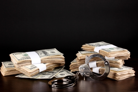 Handcuffs and packs of dollars on wooden table close-up Stock Photo - 15014649