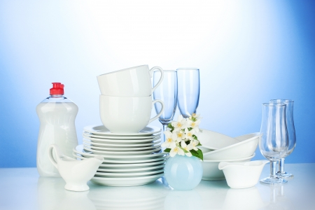 empty clean plates, glasses and cups with dishwashing liquid and flowers on blue background photo