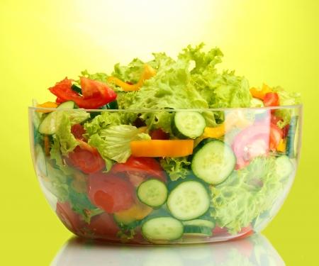 fresh vegetable salad in transparent bowl on green background photo