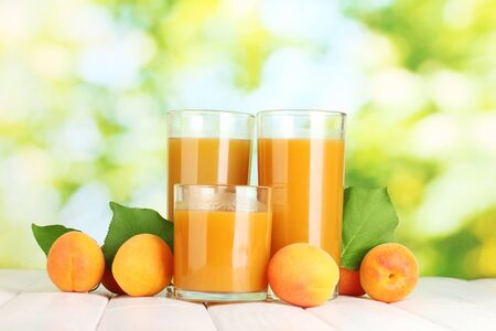 glasses of apricot juice  and fresh apricots on white wooden table on green background photo