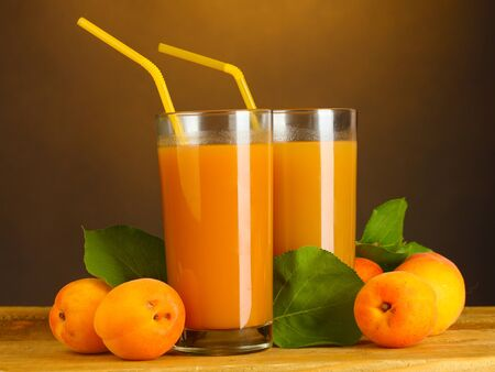 glasses of apricot juice on wooden table on brown background Stock Photo - 15060676