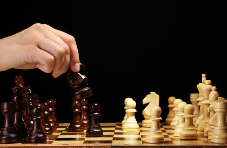 games hand: Chess board with chess pieces isolated on black