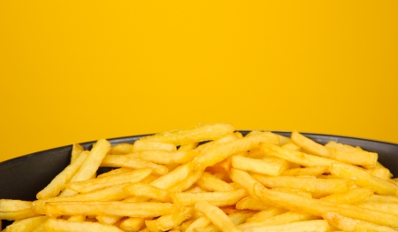 Potatoes fries in the pan on yellow background close-up photo