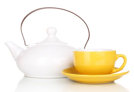 Yellow cup with saucer and teapot isolated on white photo