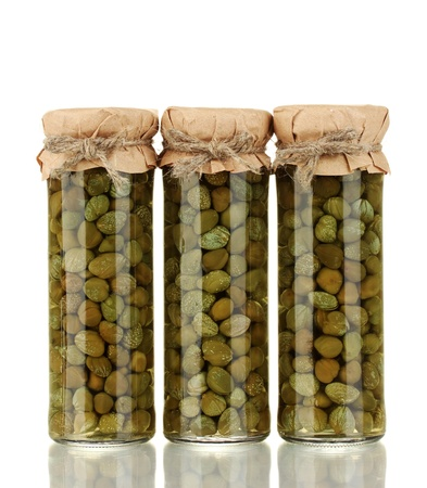 Glass jar with tinned capers isolated on white photo