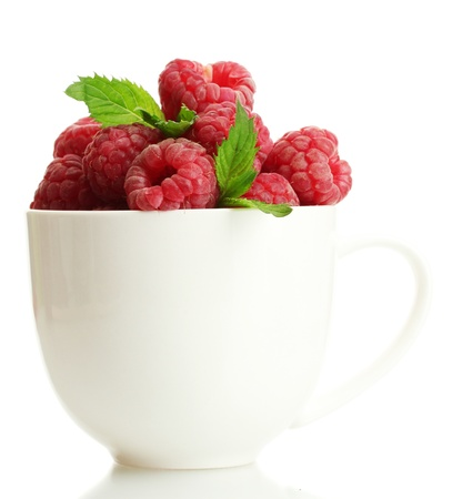 ripe raspberries with mint in cup isolated on white photo