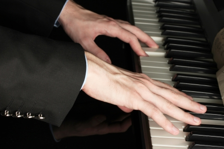 piano player: man hands playing piano Stock Photo