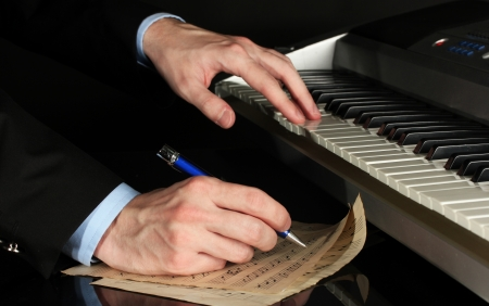composer: man hands playing piano and writes on parer for notes