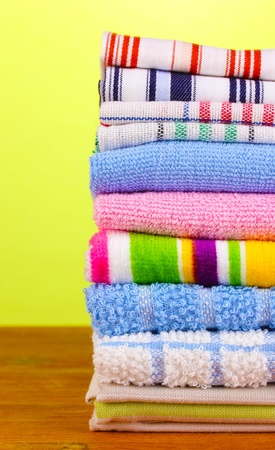 kitchen towels on wooden table on green background close-up photo