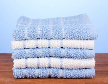kitchen towels on wooden table on blue background close-up photo