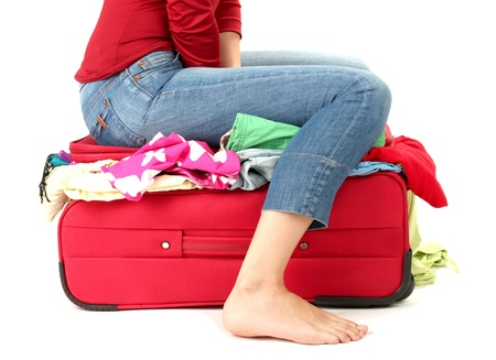 packed: The girl is trying to close suitcase crammed on white background Stock Photo