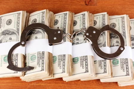 Handcuffs on the packs of dollars on wooden table close-up Stock Photo - 15048643