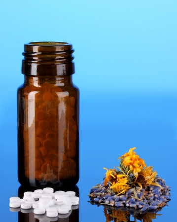bottle with pills and herbs on blue background. concept of homeopathy photo