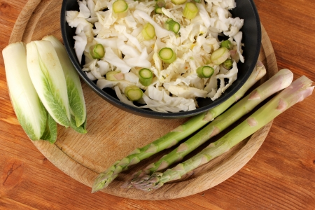 nutritiously: Pan with coleslaw, asparagus and chicory on wooden table background