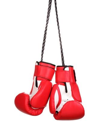 Guantes de boxeo rojos colgando aislado en blanco Foto de archivo