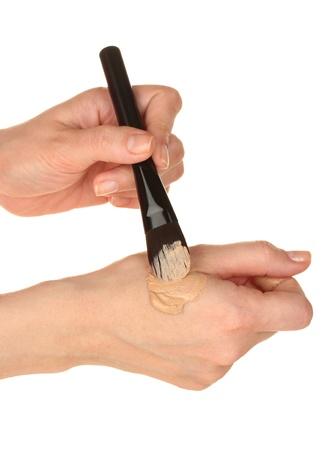 concealer: Donna che applica concealer a portata di mano su sfondo bianco close-up Archivio Fotografico
