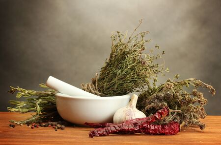 thyme: dried herbs in mortar and vegetables, on wooden table on grey background