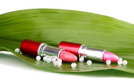 lipsticks on green leaf isolated on white photo