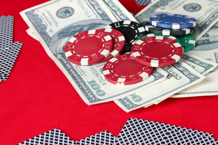 Playing cards, poker chips and dollars on a red table photo