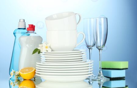 empty clean plates, glasses and cups with dishwashing liquid, sponges and lemon on blue background photo