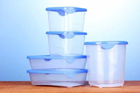Plastic containers for food on wooden table on blue background photo