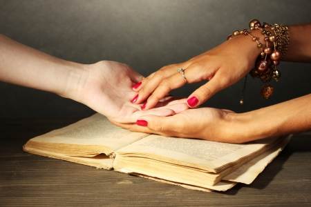 psychic reading: reading the lines hand in a womans hands on grey backcground