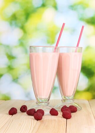Raspberry milk shakes on wooden table on bright background photo