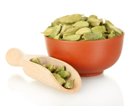 green cardamom in ceramical bowl isolated on white close-up
