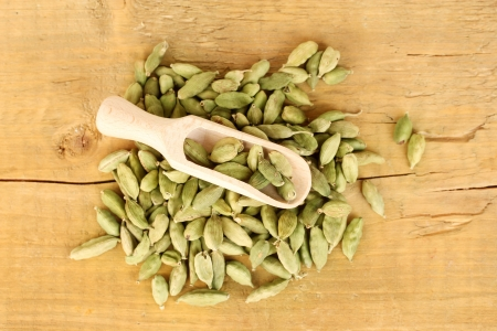 green cardamom in wooden spoon on wooden background close-up